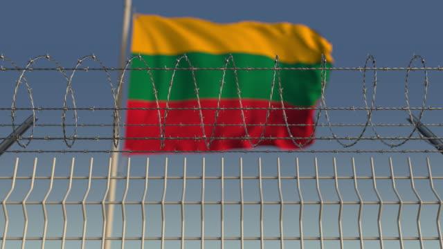 schwenkende flagge von litauen hinter stacheldrahtzaun - litauen stock-videos und b-roll-filmmaterial