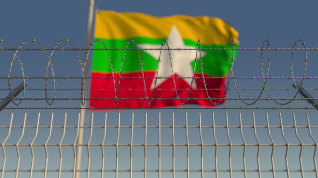 Waving flag of Myanmar behind barbed wire fence