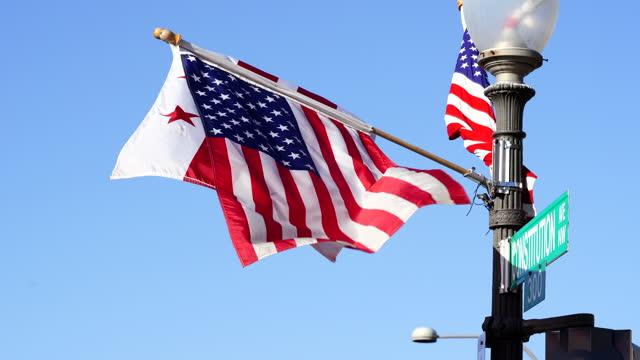 vídeos y material grabado en eventos de stock de ondeando banderas del distrito de columbia y ee.uu. en la avenida de la construcción fondo del cielo azul. - inauguration