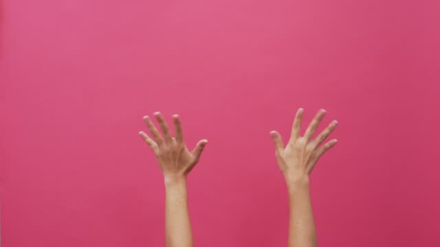 vídeos de stock e filmes b-roll de waving hands on isolated pink background 4k - membro humano