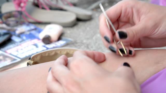 vídeos de stock e filmes b-roll de depilação das pernas com pinças e alicates, para depilar - puxar cabelos