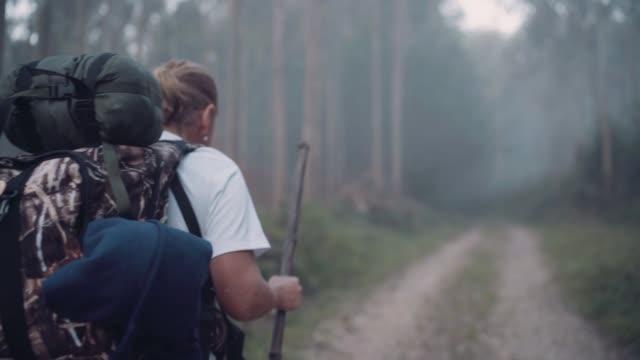 way of saint james pilgrim backpacker kvinna går genom vägen genom eukalyptus skogen tillbaka visa slow motion film. - pilgrimsfärd bildbanksvideor och videomaterial från bakom kulisserna