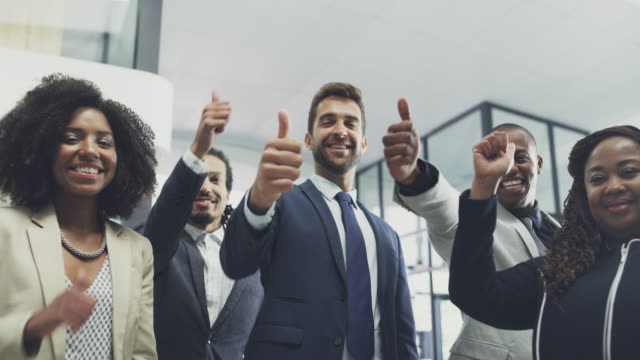 We all approve! 4k video footage of a group of businesspeople showing thumbs up together in an office representing stock videos & royalty-free footage