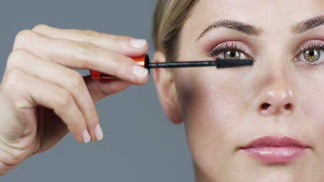 We all need a little lift now and then 4k video footage of an attractive young woman applying mascara against a grey studio background mascara stock videos & royalty-free footage