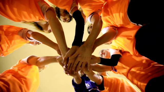 We can do this Together Slow motion Video of Group of female volleyball players and their male coach stacking hands,directly below volleyball sport stock videos & royalty-free footage