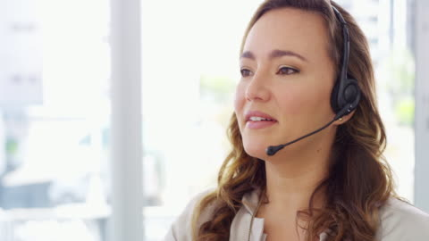 We consistently meet and exceed our customer's expectations 4k video footage of a young woman using a computer and headset in a modern office service stock videos & royalty-free footage