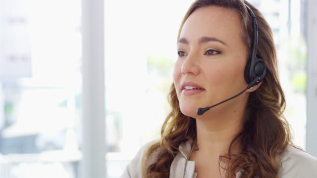 We consistently meet and exceed our customer's expectations 4k video footage of a young woman using a computer and headset in a modern office call centre videos stock videos & royalty-free footage