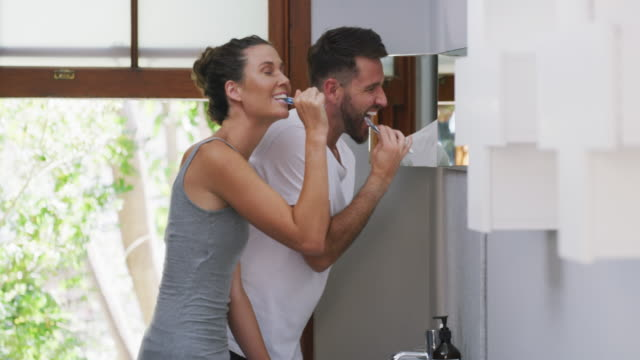 We do everything together 4k video footage of a young attractive married couple brushing their teeth together in the bathroom at home bathroom stock videos & royalty-free footage
