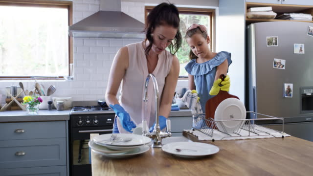 We makes sure that everything is a fun activity 4k video footage of a young girl helping her mother with the dishes at home washing dishes stock videos & royalty-free footage