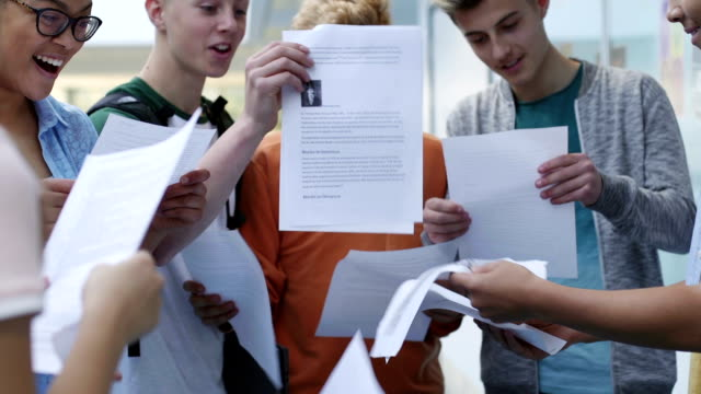 We Passed! Group of teenage students are getting their exam results. They are comparing grades happily. test results stock videos & royalty-free footage
