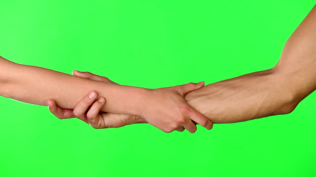 We stand united Hd video footage of two people clasping each other's wrists if front of a green screen in a studio heterosexual couple stock videos & royalty-free footage