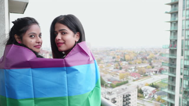 We support the LGBTQ movement! - Girls wrapped in the rainbow flag smiling at the camera