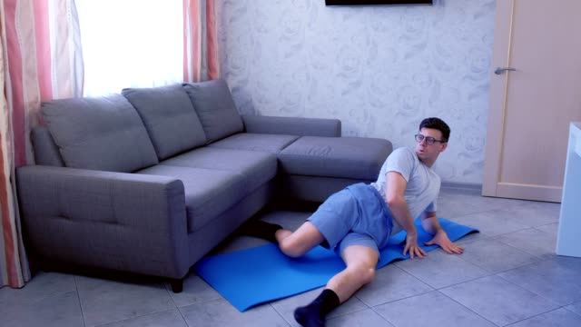 Weak nerd man is doing funny exercises for legs laying on the floor at home. Sport humor concept. video