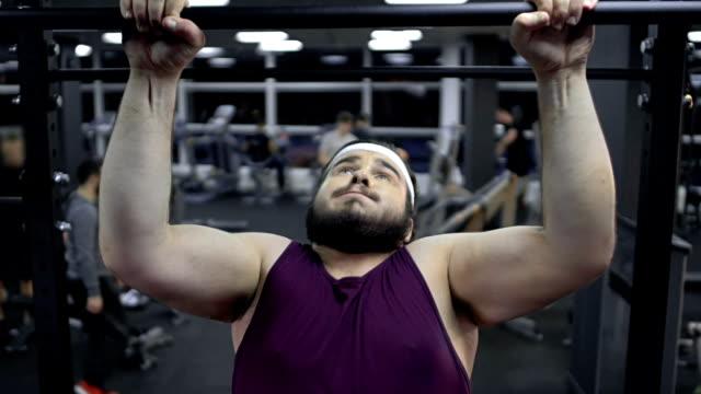 maschio obeso debole che cerca di tirare su in palestra, mancanza di fiducia in se stessi, insicurezze - fragilità video stock e b–roll
