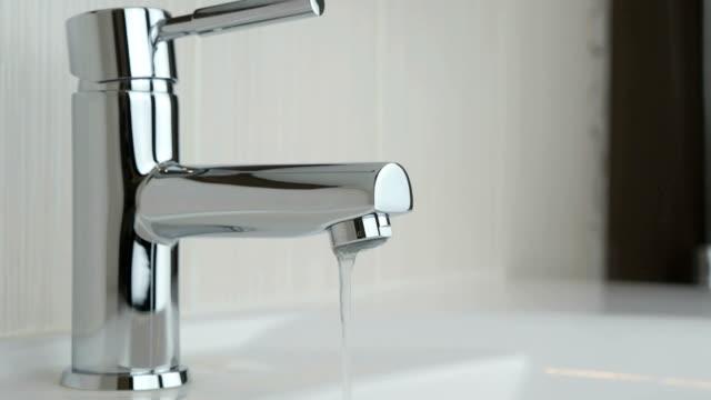 pressione dell'acqua debole che scorre da un rubinetto cromato - fragilità video stock e b–roll