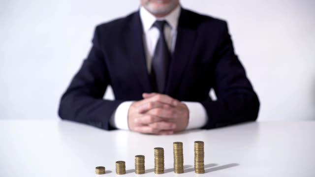 reicher mann sitzt vor münze pfähle, wachstum der einlagenzinsen, banking - billionär stock-videos und b-roll-filmmaterial