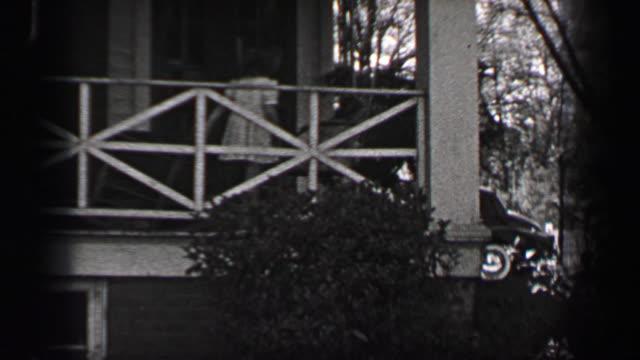 1939: wohlhabende junge mädchen in weißen formale sonne kleid verlassen südstaaten veranda um besucher zu begrüßen. - editorial videos stock-videos und b-roll-filmmaterial