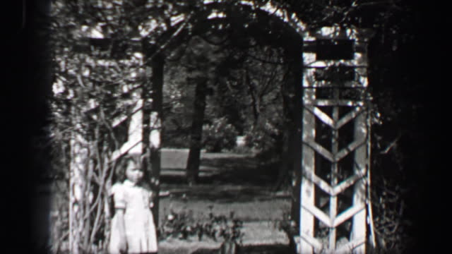 1939: Wealthy young girls play in white formal sundresses under arch garden pergola. video