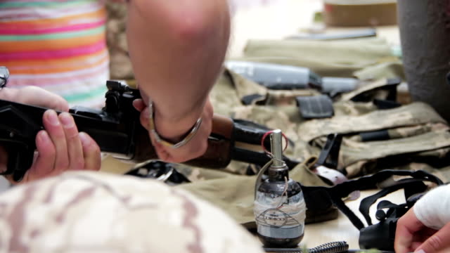 Weapons, Automatic Machines, Grenades, Ammunition, Bullets are on the Table, and Military Weapons, Automatic Machines, Grenades, Ammunition, Helmets, anti-tank Mines, Bullets are on the Table and Military. Dismantling machine military camouflage uniforms. Full HD 1920 x 1080, 29,97 fps gun stock videos & royalty-free footage