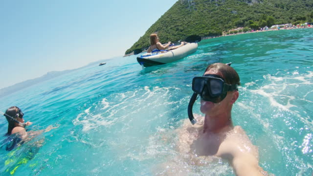 ms wearable camera point of view man jumping into sunny blue ocean,peljesac,croatia - vacanze video stock e b–roll
