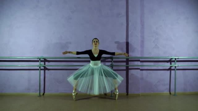 tragen spitzen schuhen ballerina tänze in der nähe von barre in tanzsaal - gymnastikanzug stock-videos und b-roll-filmmaterial
