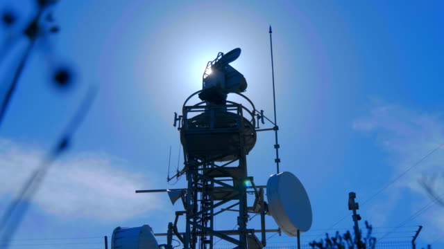 Weather radar with a rotating radiodetection antenna on top of a mountain Weather radar with a rotating radiodetection antenna on top of a mountain collects weather data from whole around area against a blue sky. Shot in motion meteorology stock videos & royalty-free footage