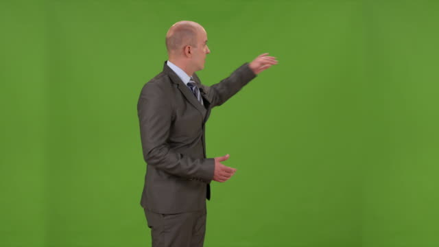 HD: Weathercaster On A Chroma Key Background HD1080p: Well dressed businessman showing/pointing on a chroma-key background while presenting/moderating something in the studio. pointing stock videos & royalty-free footage