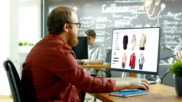 Web Designer Works on a Website for Online Retail Clothing Shop. He and Colleagues Work in Styish Creative Agency Studio.