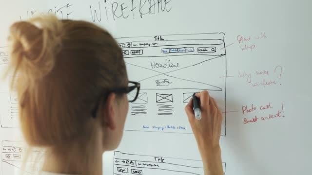 vídeos de stock, filmes e b-roll de desenvolvimento web - designer ui ux trabalhando em novo wireframe do site - designer profissional