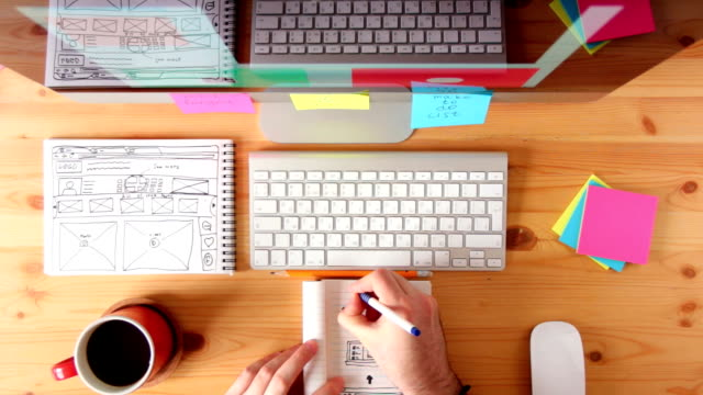 webmaster draws the future layout of the web pages in the sketch book - designers video stock e b–roll