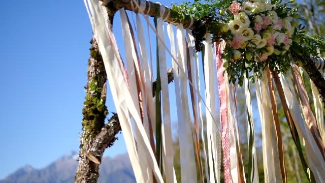 Arco de la boda de madera nudos con cintas y flores. Las montañas y el bosque de fondo - vídeo
