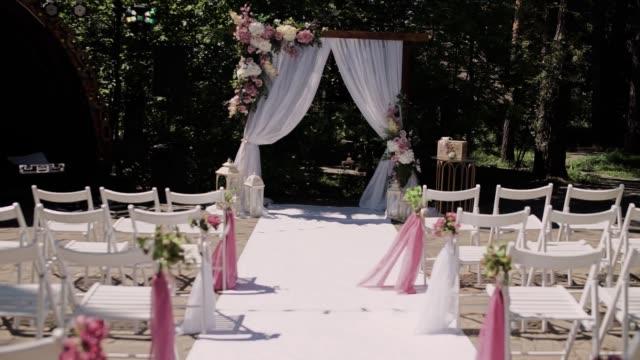 vidéos et rushes de arc de mariage avec des chaises décorées avec des fleurs - banquet