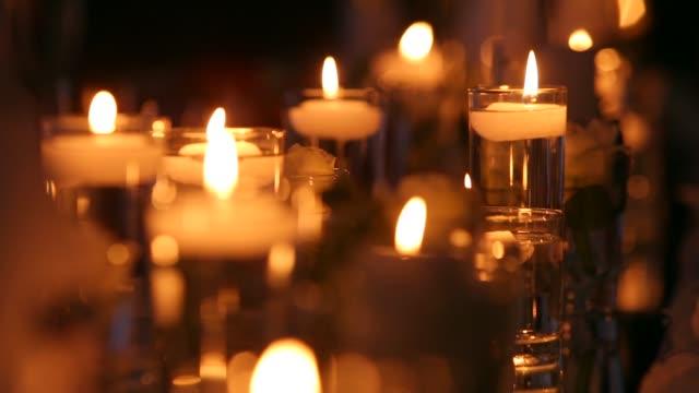 婚禮宴會廳內部細節與裝飾餐桌設置在餐廳。蠟燭和白色花瓣點綴著玫瑰花, 玻璃花瓶裡裝滿了水。宏觀 - 浪漫 個影片檔及 b 捲影像