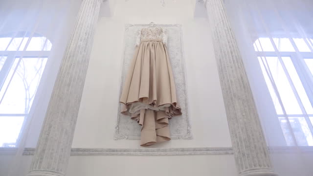 Wedding beige dress hanging on wall inside space room in big house video