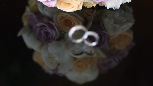 wedding bouquet and rings on a black background
