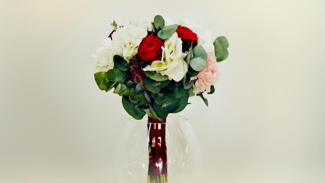 A wedding bouquet of hydrangea, pion-shaped rose, carnation and eucalyptus greens. Bouquet in rotation
