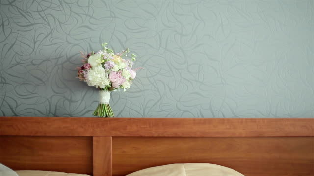 Wedding bouquet on the gray wall background above the bed video