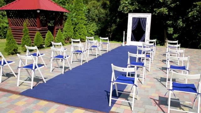 vidéos et rushes de cérémonie de mariage à l'extérieur du restaurant. chaises et passerelle bleue pour les mariées et les invités - banquet