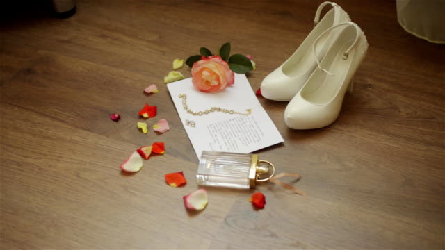 Wedding composition. Morning of the bride. Close up of wedding white shoes on high heels. Rings, rose petals and wedding invitations on the floor. video