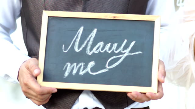 Wedding concept. Will you marry me question handwritten on blackboard shown by young men.
