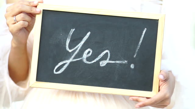 "Wedding concept. Word ""Yes"" written on blackboard shown by young women."