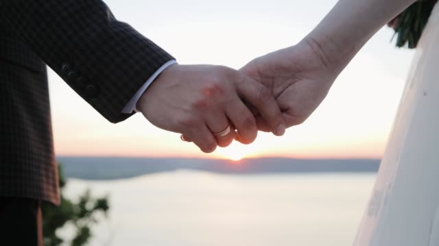 wedding couple holds hands at sunset. the sun's rays shine through their fingers. love, happiness and friendship. hands close up at sunrise. - young couple wedding friends video stock e b–roll