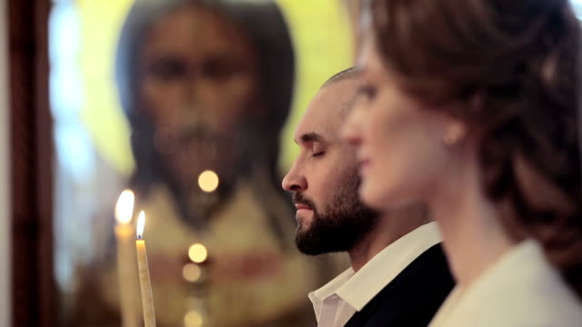 Wedding couple in a church with candles video