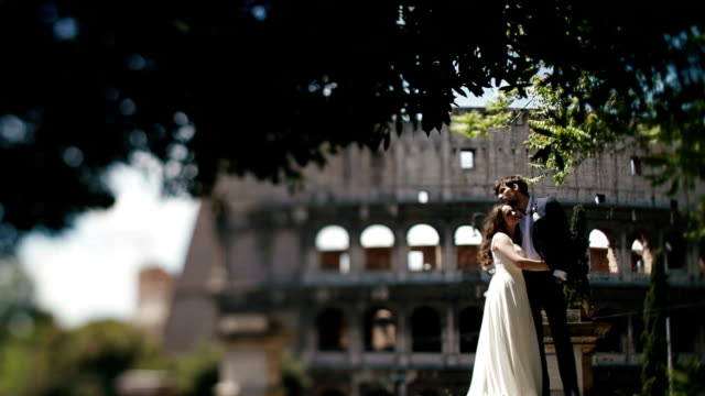 Wedding couple in Rome posing near the Coliseum. Beautiful bride leaning to shoulder of her new husband. Honeymoon in Italy, Europe video