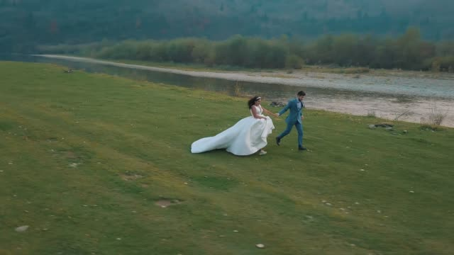 Wedding couple running near mountain river. Groom and bride. Arial view