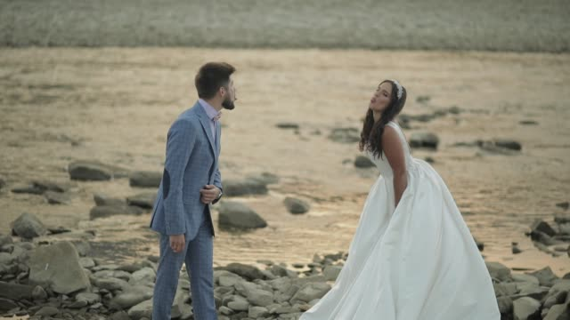wedding couple standing near mountain river. groom and bride making faces - rappresentazione umana video stock e b–roll