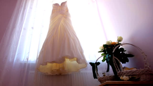Wedding day. bride's dress hangs on the window video