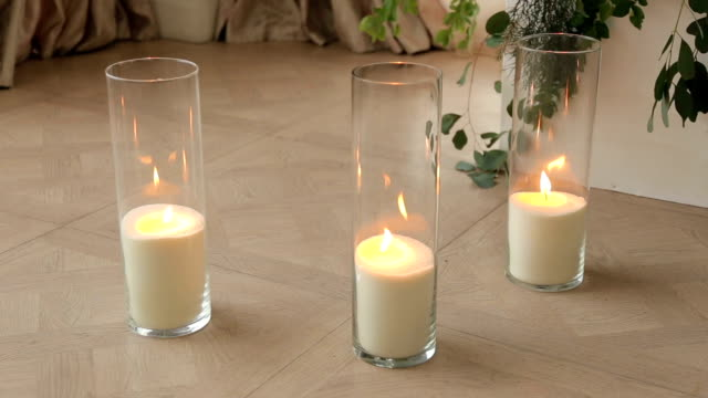 Wedding decor, candles in glass flasks standing on the floor.