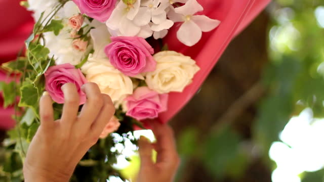 Wedding decor setting. Florists and decorators making rustic floristic decor with pink roses flower compositions with hands. FullHD 1080p footage video