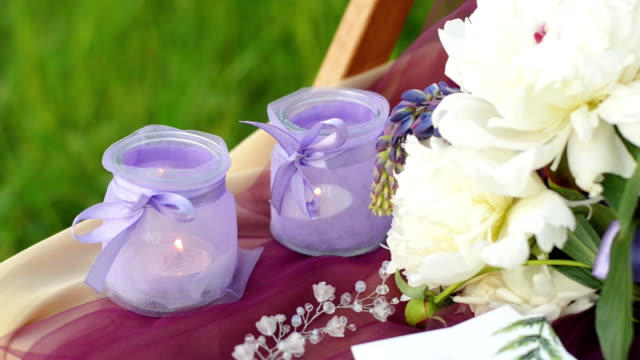 Wedding decoration ceremony in purple colors. Candlesticks with burning candles. Wedding wreath and bouquet of lupines and peons. video
